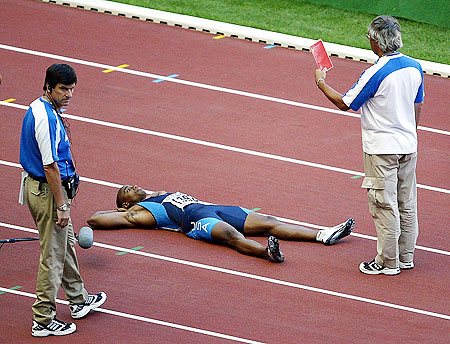 Jon Drummond of the USA lies on the track in protest after being disqualified for a false start