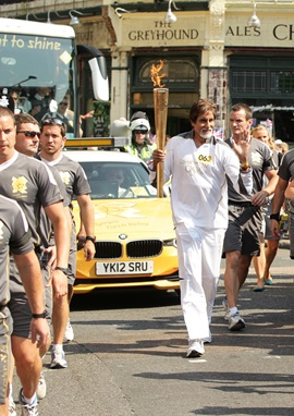 Amitabh Bachchan carries the Olympic Flame on the Torch Relay leg between The City of London and Southwark during Day 69 of the London 2012 Olympic Torch Relay
