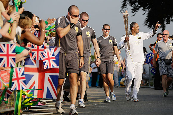 Former decathlon world record holder and Olympic gold medallist Daley Thompson carries the Olympic Torch at the relay on Thursday