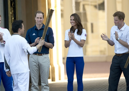 Catherine, Duchess of Cambridge, Prince William, Duke of Cambridge and Prince Harry applaud Wai-Ming as the Olympic Torch comes to Buckingham Palace