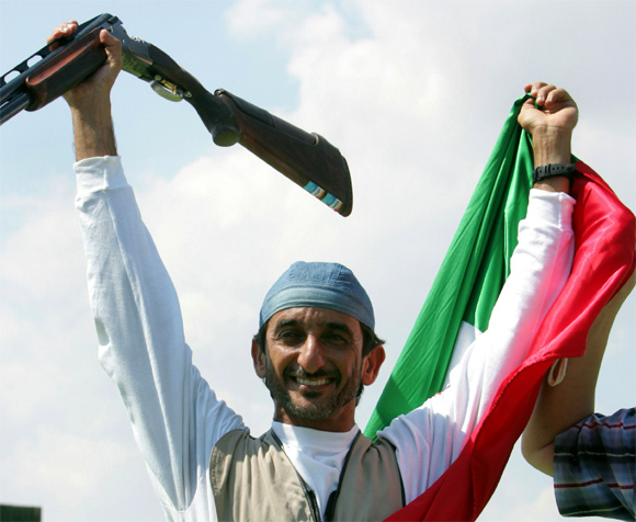 Sheikh Ahmad Al-maktoum of United Arab Emirates celebrates as he hold aloft his national flag after he won the men's double trap final of the Athens 2004 Olympic Games