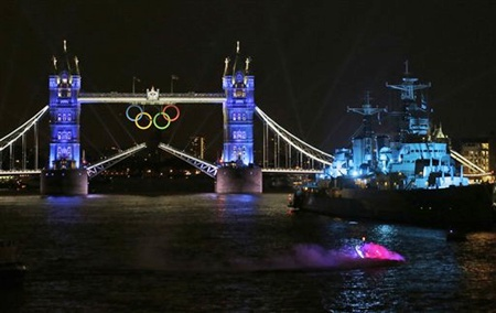 A speedboat, bottom right, carrying the Olympic Flame
