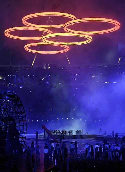 Illuminated Olympic rings hang over performing actors during the Opening
