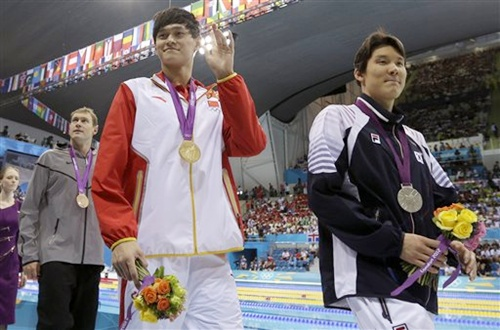 Gold medal winner China's Sun Yang waves with silver medal winner South Korea's Park Tae-hwan, right, and United States' Peter Vanderkaay