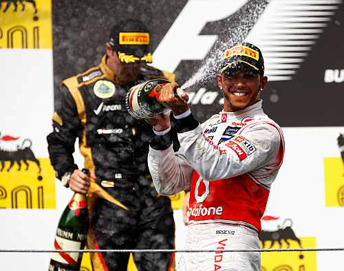 First placed Lewis Hamilton (R) of Great Britain and McLaren celebrates on the podium with second placed Kimi Raikkonen (L)of Finland and Lotus following the Hungarian Formula One Grand Prix