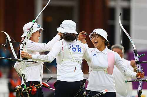 Hyeonju Choi, Bobae Ki and Sung Jin Lee of Korea celebrate victory in the Women's Team Archery Gold medal match between Korea and China