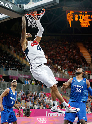 Tyson Chandler of United States dunks the ball as France's Tony Parker (left) and a teammate watch during their match at the London Olympics on Sunday