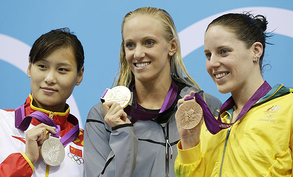 Silver medallist China's Lu Ying, Gold medallist American Dana Vollmer and Bronze medallist Australia's Alicia Coutts on the podium after winning the women's 100-meter butterfly swimming final on Sunday