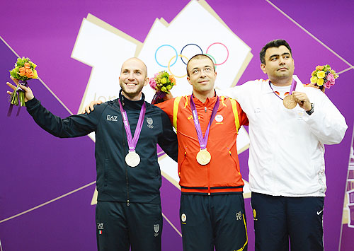 Gold medallist Alin George Moldoveanu (centre) of Romania, silver medallist Niccolo Campriani of Italy (left) and bronze medallist Gagan Narang of India pose on the podium