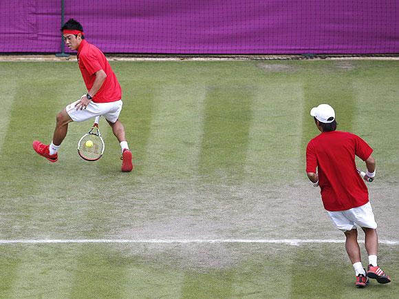 Japan's Go Soeda watches as Kei Nishikori hits a return through the legs against Switzerland's Roger Federer and Stanislas Wawrinka