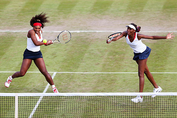 Venus Williams (right) of United States hits a forehand next to her partner Serena Williams during their Women's doubles match against Sorana Cirstea and Simona Halep of Romania