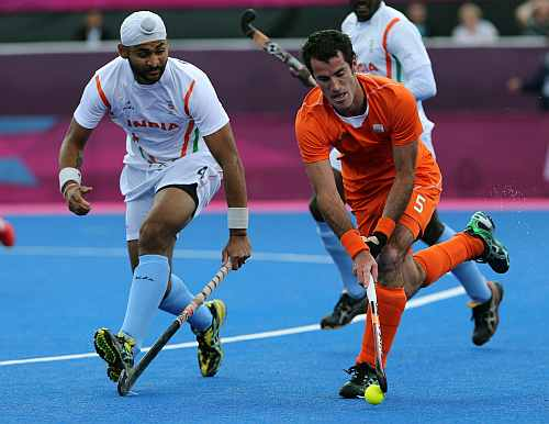 The Netherlands' Marcel Balkestein and India's Sandeep Singh vie for the ball