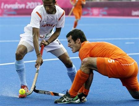 The Netherlands' Marcel Balkestein, right, and India's Sunil SV battle for ball possession