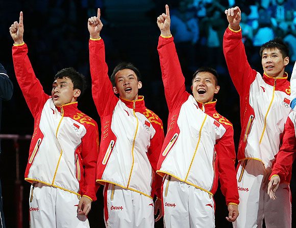 Gold medalists Zhe Feng, Weiyang Guo, Yibing Chen, Chenglong Zhang and Kai Zou of China celebrate on the podium during the medal ceremony in the Artistic Gymnastics Men's Team final on Monday