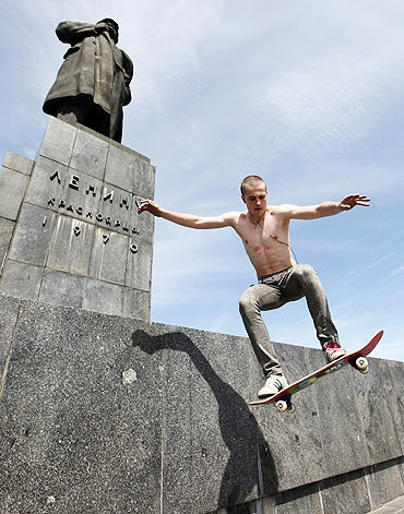 An amateur skateboarder jumps in front of a monument of Vladimir Ilici Lenin, the founder of the former Soviet Union in Krasnoyarsk