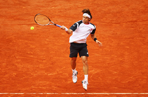 David Ferrer of Spain plays a forehand in his men's singles fourth round match against Marcel Granollers of Spain