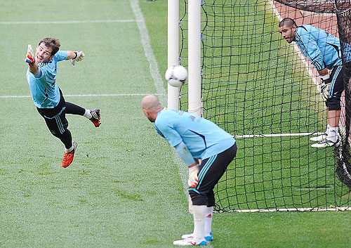 Iker Casillas (left) tries to save a shot while Pepe Reina (centre) and Victor Valdes look on during a training session