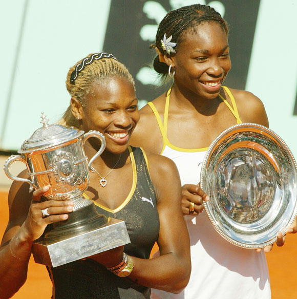 Serena Williams (left) and sister Venus pose with their trophies after the 2002 French Open final