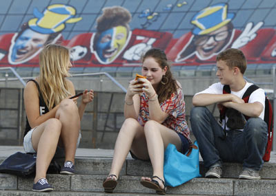 Teenagers sit in front of EURO-2012-themed decoration in Kiev