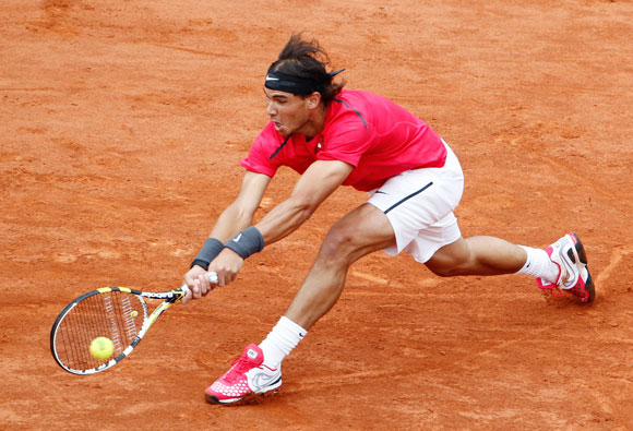 Rafael Nadal of Spain returns the ball to his compatriot Nicolas Almagro during their quarter-final match at the French Open