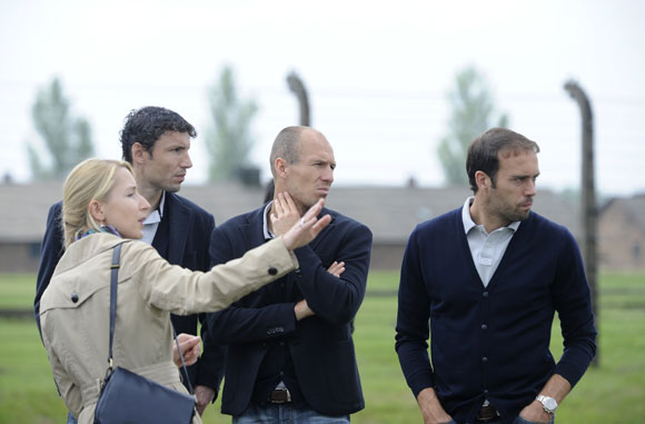 Netherlands' players Mark van Bommel, Arjen Robben and Joris Mathijsen (2nd L-R) listen to a guide during their visit to the Auschwitz-Birkenau former Nazi concentration camp