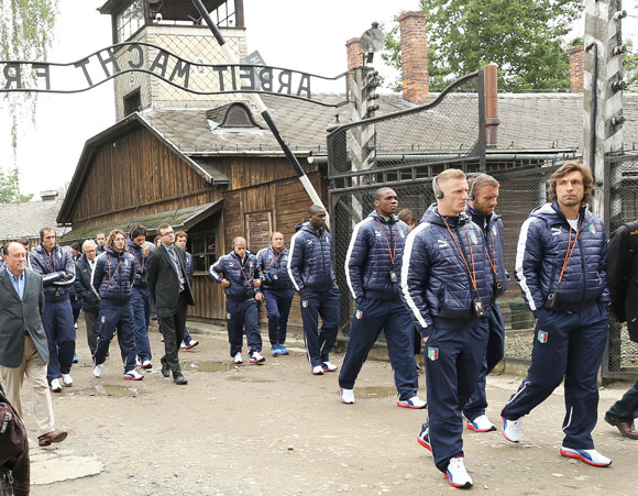 Italy's national soccer players walk through Auschwitz's notorious gate