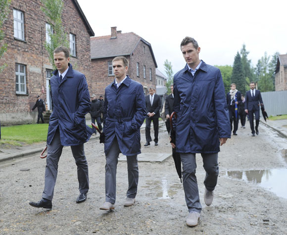 Germany team manager Oliver Bierhoff, captain Philipp Lahm and forward Miroslav Klose (L-R) walk through Auschwitz former concentration camp