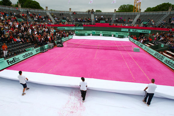 Groundstaff unveil a pink clay court prior to the women's legends doubles semi-final