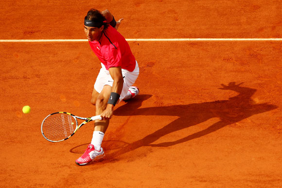 Rafael Nadal of Spain slides across the clay to play a backhand during his men's singles match at the French Open