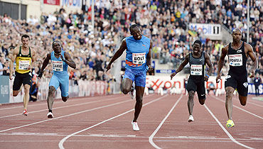 Usain Bolt of Jamaica (centre) crosses the line to pip Asafa Powell (right) and win the men's 100m race during the Diamond League athletics competition at the Bislett Stadium in Oslo on Thursday