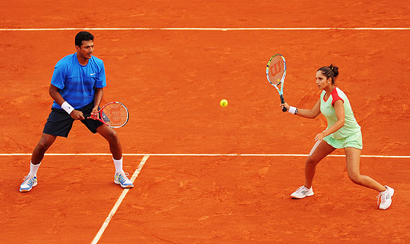 Sania Mirza plays a return as Mahesh Bhupathi watches during their mixed doubles final on Thursday