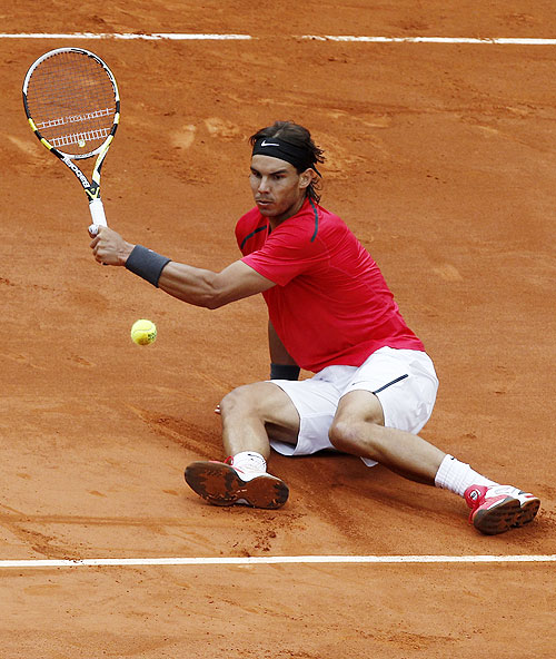 Rafael Nadal falls as he returns against David Ferrer