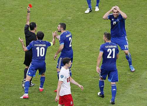 Greece's players react on a red card for Sokratis Papastathopoulos (R) during the Group A Euro 2012 soccer match against Poland at the National Stadium