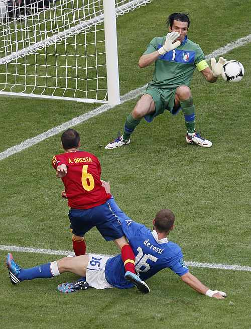 Spain's Andres Iniesta (L) tries to score against Italy's goalkeeper Gianluigi Buffon (R) and Daniele De Rossi during their Group C Euro 2012 soccer match at the PGE Arena