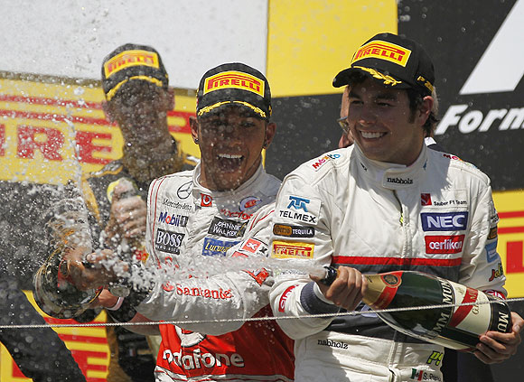McLaren's Lewis Hamilton (centre) and third placed Sauber's Sergio Perez spray champagne on the podium