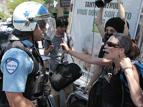 A protester confronts police during demonstrations aimed to disrupt the Canadian GP