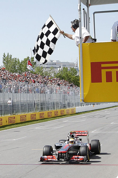 McLaren'sLewis Hamilton takes the chequered flag to win the Canadian GP