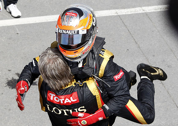 Lotus F1 driver Romain Grosjean of France hugs a crew member after the Canadian GP