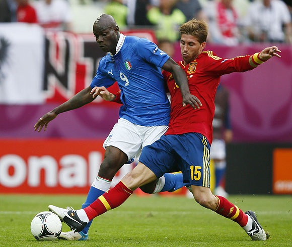 Italy's Mario Balotelli is challenged by Spain's Sergio Ramos (right)