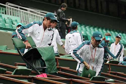 Workers clean the tribune of the Philippe Chartrier court as the men's singles final match between Rafael Nadal and Novak Djokovic was suspended for the day