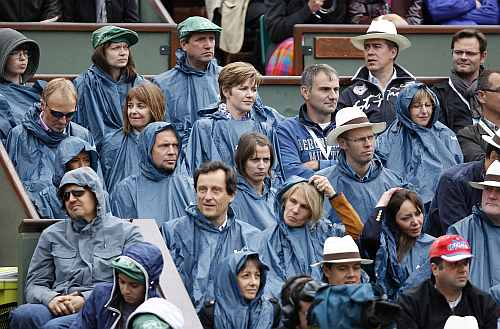 Spectators protect themselves from the rain with raincoats during the men's singles final match during the French Open