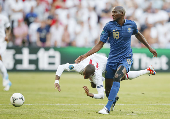 England's Ashley Young collides with France's Alou Diarra (R) during the Euro 2012 Group D soccer match at Donbass Arena in Donetsk