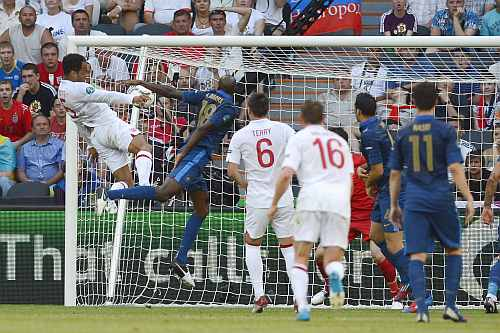 England's Joleon Lescott (L) scores past France's Alou Diarra during their Group D Euro 2012 soccer match at the Donbass Arena in Donetsk