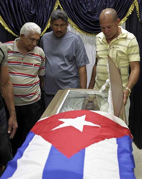 People pay their respects at the coffin of Cuban boxer Teofilo Stevenson at a funeral home in Havana
