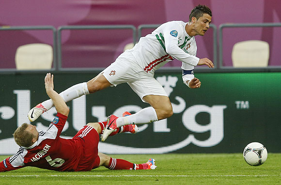 Portugal's Cristiano Ronaldo is fouled by Denmark's Lars Jacobsen