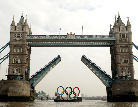 The Tower Bridge opens as the Olympic rings pass through on The River Thames in London