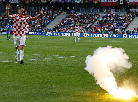 Croatia's Ognjen Vukojevic reacts after a flare is thrown on the pitch