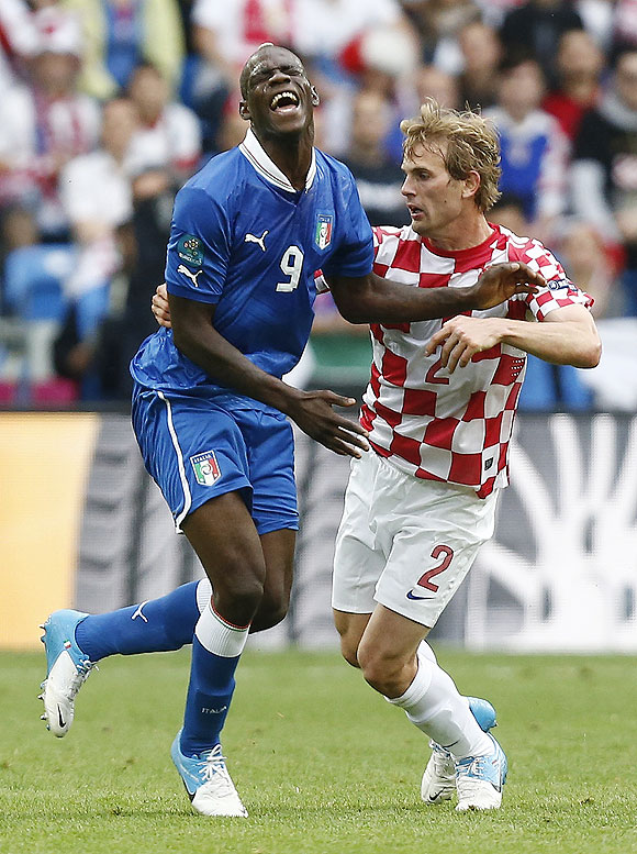 Italy's Mario Balotelli (left) grimaces as he is challenged by Croatia's Ivan Strinic