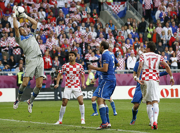 Italy's goalkeeper Gianluigi Buffon (left) makes a save as Croatia's Eduardo (centre) and Mario Mandzukic look on