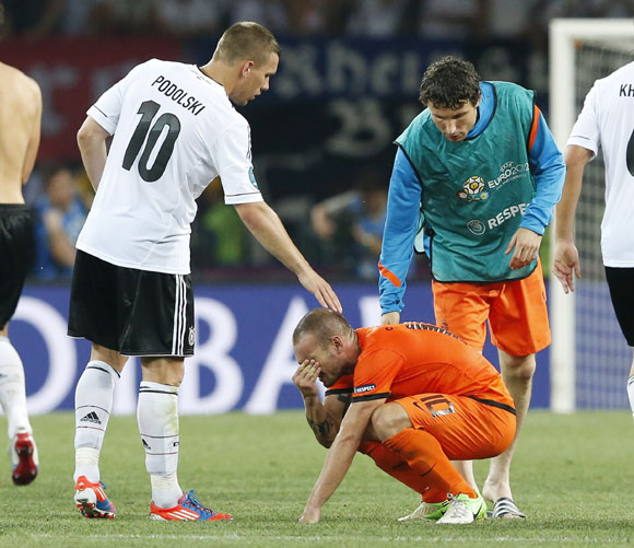 Germany's Lukas Podolski (left) and Netherlands' Mark van Bommel (right) comfort Netherlands' Wesley Sneijder